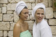 One woman wrapped in a towel laughing with another woman in a bathrobe Stock Photos