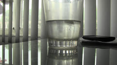 Woman picks up water glass and drinks Stock Footage