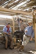 Three cowboys standing inside a wooden shed Stock Photos