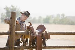 Rancher valmistelee hevonen satula aidan Kuvituskuvat