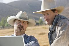 Two cowboys looking at a laptop together Stock Photos