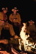 Three cowboys around a campfire - stock photo
