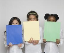 Three girls holding up multi colored paper - stock photo