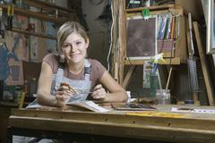 A young woman working in an art studio, portrait - stock photo