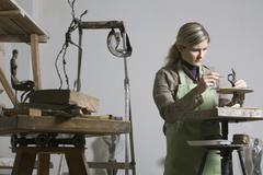 A young woman working in an art studio Stock Photos
