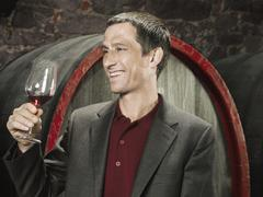 A vintner holding a glass of red wine and smiling Stock Photos