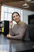 A woman wearing a headset in an office Stock Photos