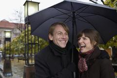 Young couple laughing under an umbrella Stock Photos