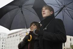Young couple holding umbrellas - stock photo