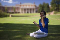 A young woman using a mobile phone on university lawn Stock Photos