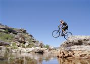 Stock Photo of A man jumping a mountain bike into a stream