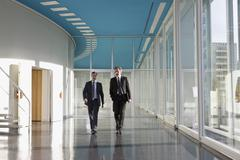 Two businessmen walking in the foyer of a convention center - stock photo