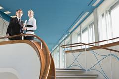 Two business people standing at the top of a staircase - stock photo