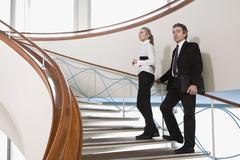 Two business people standing on a staircase Stock Photos