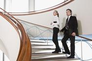 Stock Photo of Two business people standing on a staircase