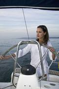 A woman at the helm of a yacht Stock Photos