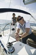 A couple adjusting the rigging on a yacht Stock Photos