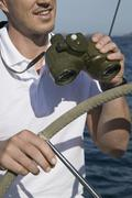 Detail of a man with binoculars at the helm of a yacht Stock Photos