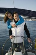 A couple embracing at the helm of a yacht - stock photo