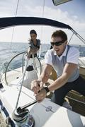 A couple adjusting the rigging on a yacht - stock photo