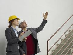 Two architects working on a construction site Stock Photos