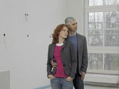 A couple standing in a their new home - stock photo