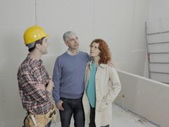 A building contractor talking with a young couple on a building site Stock Photos