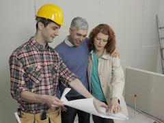A building contractor going over blueprints with a young couple Stock Photos