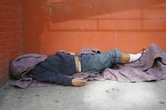 A homeless person sleeping on the floor Stock Photos