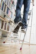A man's legs climbing up a ladder that's about to tip over - stock photo