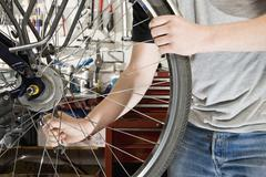 Detail of a man repairing a bike Stock Photos
