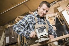 A carpenter using a sanding machine in a workshop Stock Photos