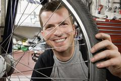 A man looking through a bicycle wheel Stock Photos