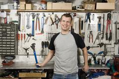 A man holding a wrench in a workshop - stock photo