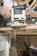 Detail of a carpenter using a sanding machine - stock photo
