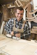 A carpenter using a plane - stock photo