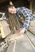 A carpenter sawing wood in a workshop - stock photo