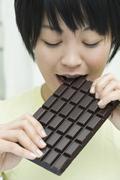 A woman biting into a chocolate bar - stock photo