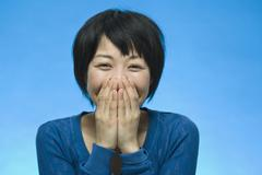 Stock Photo of Portrait of a woman laughing and covering her face
