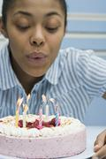 A young woman blowing out candles on a birthday cake Stock Photos