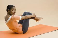 A young woman doing exercises Stock Photos