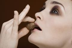 Stock Photo of A woman holding a truffle to her lips