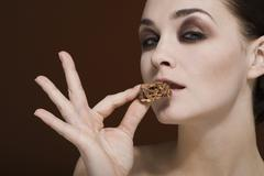 A woman holding an almond chocolate cluster to her mouth Stock Photos