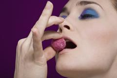 A woman tasting a Kir Royal truffle - stock photo