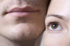 Extreme close-up of a woman's eye and man's lips - stock photo