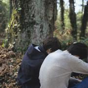 Two people sitting hunched over in a forest Stock Photos
