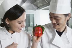 Two chefs with a bell pepper with a face on it Stock Photos