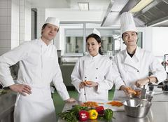 Chefs doing prep work in a commercial kitchen - stock photo