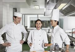 Two chefs teasing another chef - stock photo