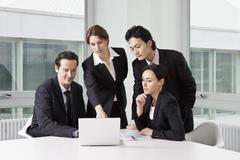 Four business people in a meeting using a laptop - stock photo